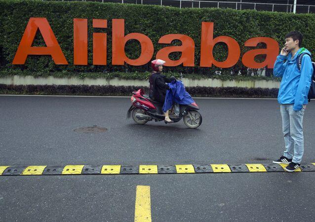 Homem e mulher em frente do logo do Alibaba Group, na sede da empresa em Hangzhou, China, 27 de maio de 2016