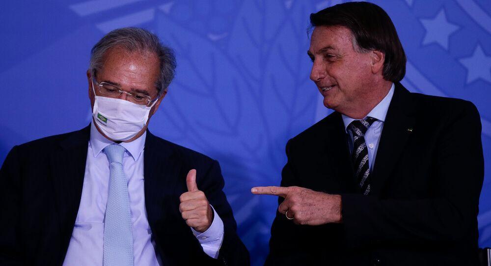Em Brasília, o presidente brasileiro, Jair Bolsonaro (à direita) aponta na direção do ministro da Economia, Paulo Guedes (à esquerda), que gesticula. Foto de arquivo
