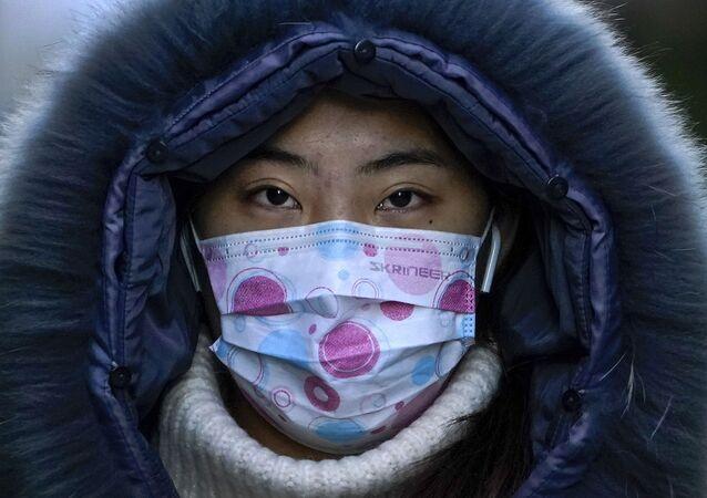 Mulher usa máscara protetora durante o inverno da capital chinesa, Pequim, 16 de dezembro de 2020