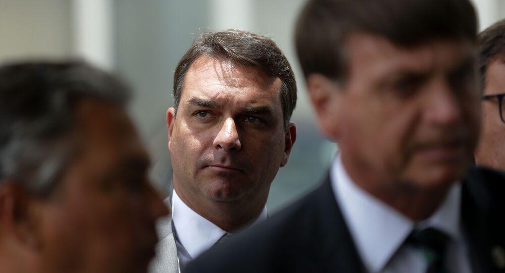 Em Brasília, o senador Flávio Bolsonaro (Republicanos-RJ), aparece ao fundo, atrás de seu pai, o presidente Jair Bolsonaro (à direita), em 27 de janeiro de 2021