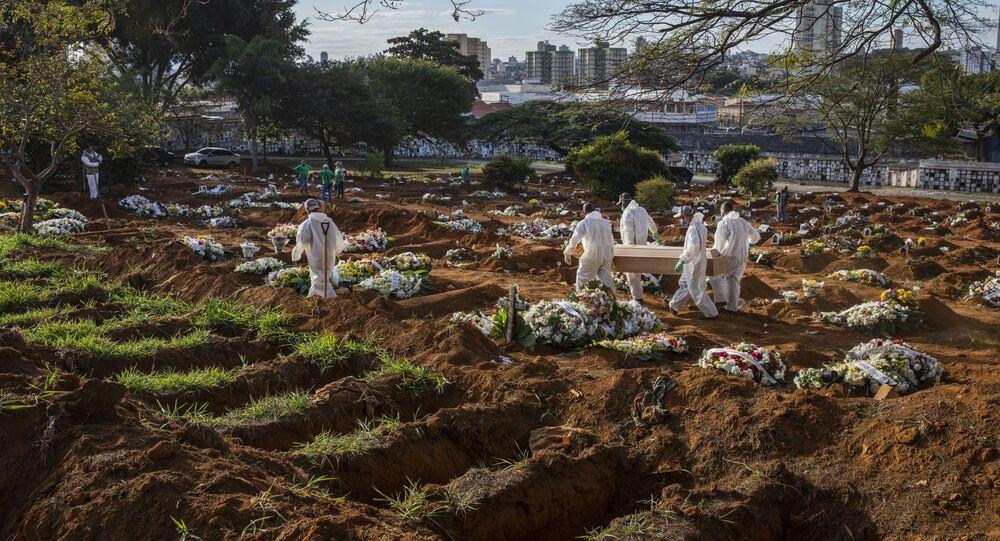 Sepultadores carregam caixão com vítima da COVID-19 no cemitério da Vila Formosa, na zona leste de São Paulo, em 16 de março de 2021