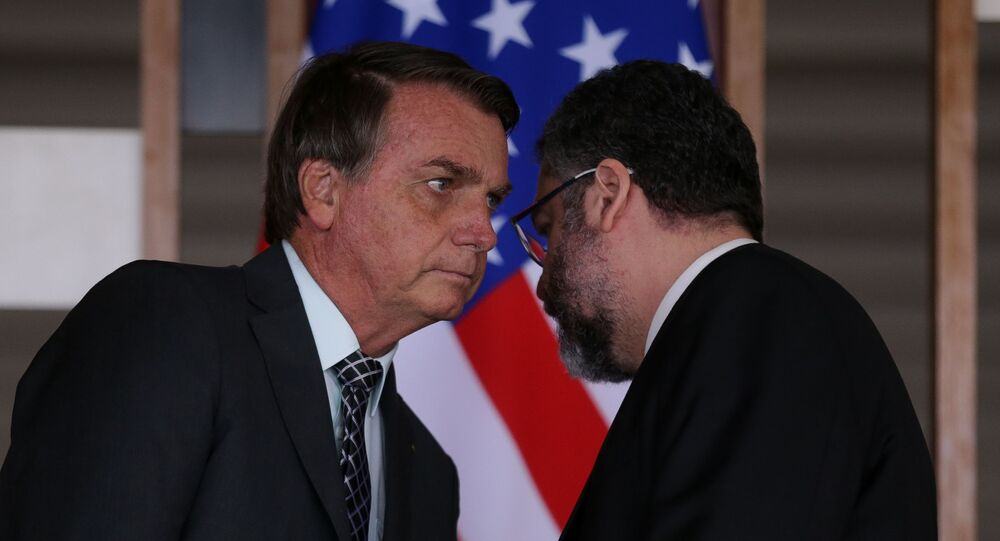 O presidente Jair Bolsonaro conversa com o ministro das Relações Exteriores, Ernesto Araújo, com a bandeira dos EUA ao fundo.