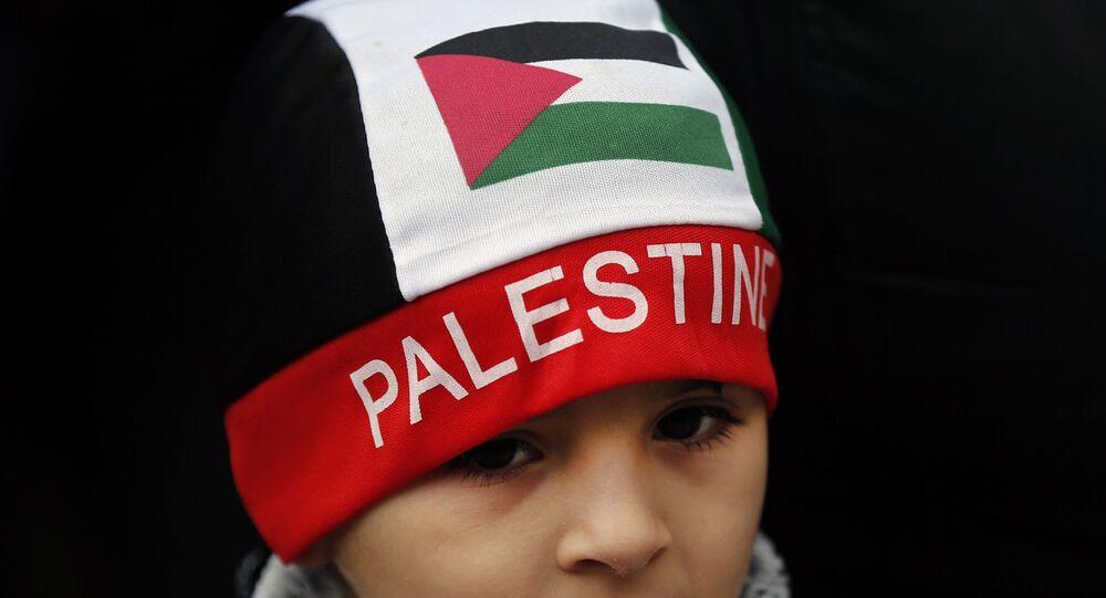 Um menino palestino com um chapéu da bandeira da Palestina