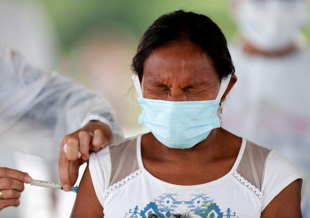Em São Gabriel da Cachoeira, no estado brasileiro do Amazonas, uma mulher indígena do grupo Hupda recebe uma dose de vacina contra a COVID-19, em 3 de março de 2021