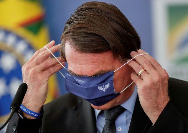 Presidente do Brasil, Jair Bolsonaro, coloca máscara durante cerimônia no Palácio do Planalto, Brasília, 22 de março de 2021