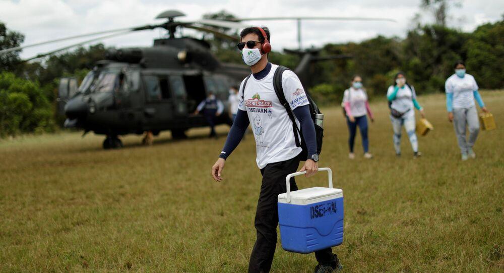 Funcionário de saúde carrega lote com CoronaVac após desembarcar de helicóptero na aldeia Tacarua Igarapé, na cidade de São Gabriel da Cachoeira, no Amazonas