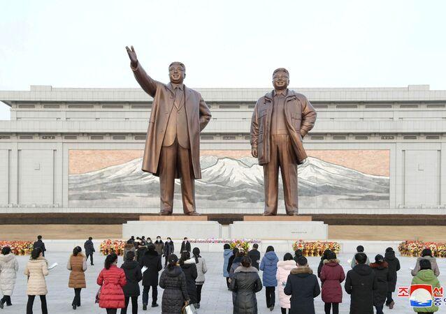 Pessoas depositam oferendas florais diante do monumento com as estátuas de bronze dos líderes Kim Il-sung e Kim Jong-il em Pyongyang