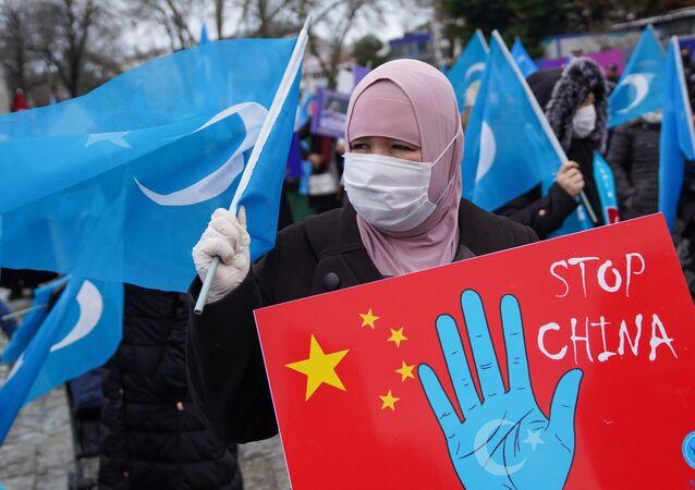 Manifestante exibe bandeira do Turquestão Oriental durante protesto contra visita do chanceler chinês à Turquia