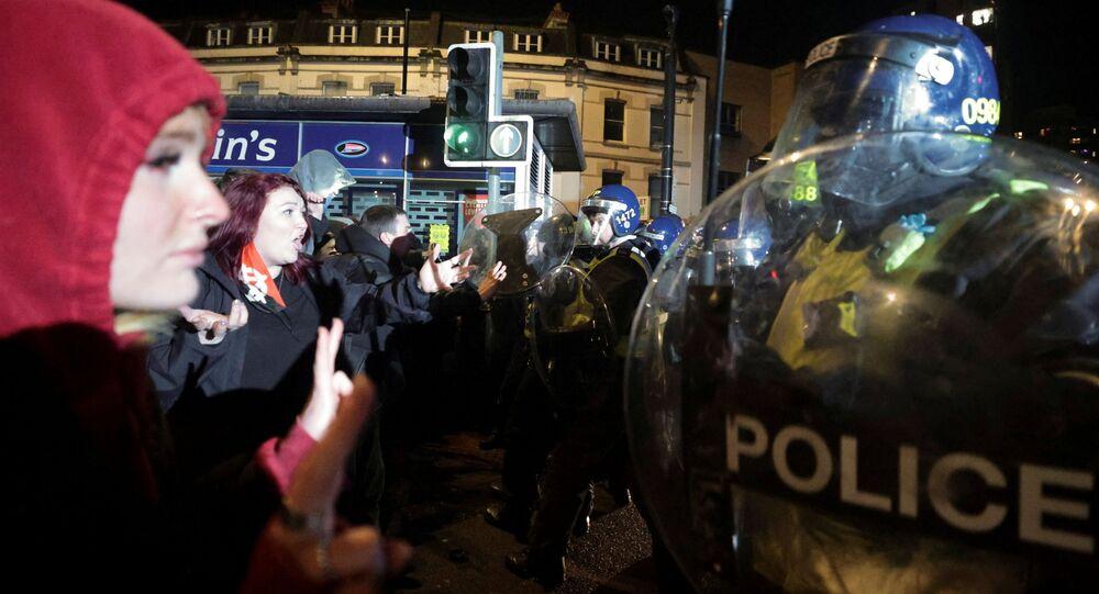 Manifestantes gesticulam na frente de policiais durante um protesto contra nova proposta de lei de policiamento, em Bristol, Inglaterra, em 26 de março de 2021.