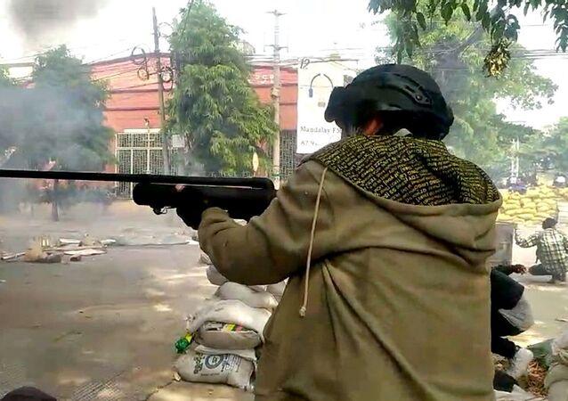 Manifestante dispara durante protesto contra militares em Mianmar, 27 de março de 2021