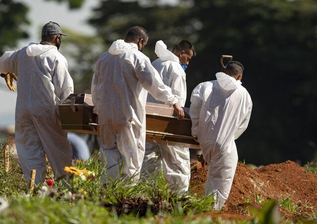 Coveiros completamente protegidos enquanto carregam caixão de uma das vítimas da COVID-19 no cemitério da Vila Formosa, em São Paulo, 24 de março de 2021