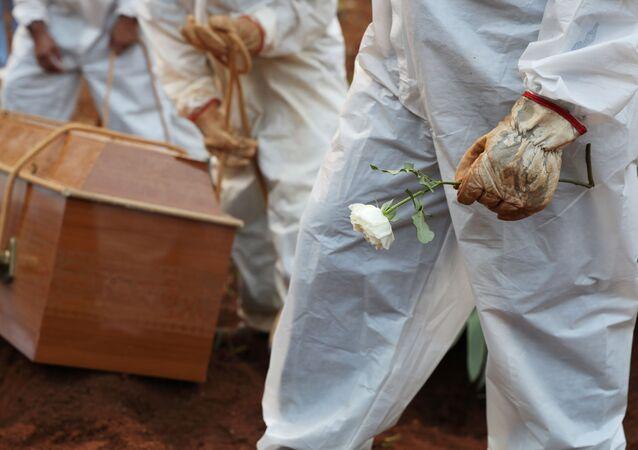 Coveiro com traje de proteção segura flor durante enterro de pessoa falecida por COVID-19 no Cemitério da Vila Formosa, em São Paulo, no Brasil, no dia 23 de março de 2021