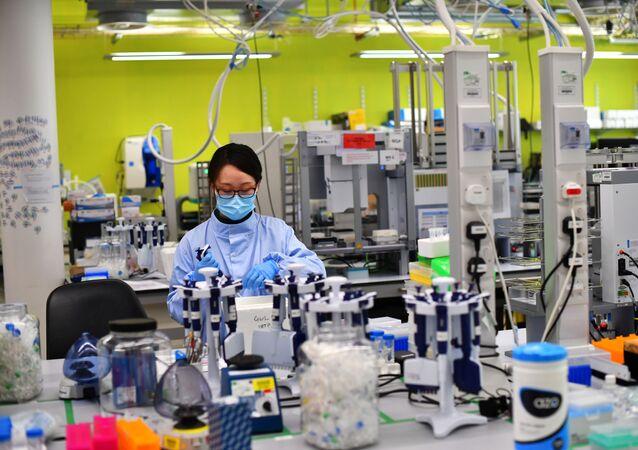Cientistas trabalham no laboratório onde sequenciam os genomas do novo coronavírus no COVID-19 Genomics UK no Instituto Wellcome Sanger, Reino Unido, 12 de março de 2021