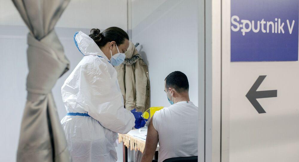 Em Belgrado, na Sérvia, um homem é vacinado contra COVID-19 com a vacina russa Sputnik V, em 31 de março de 2021