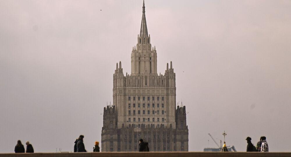 Transeuntes na ponte em Moscou. Ao fundo, o edifício do Ministério das Relações Exteriores da Rússia