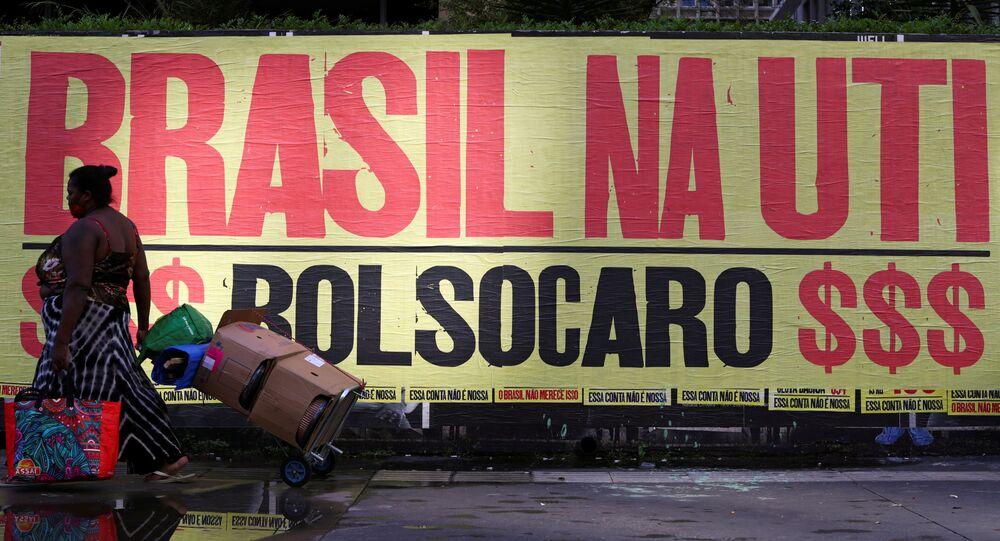 Mulher caminha em frente a uma faixa que diz: Brasil na UTI, em referência ao presidente Jair Bolsonaro e a alta dos preços dos produtos básicos em São Paulo, 8 de março de 2021