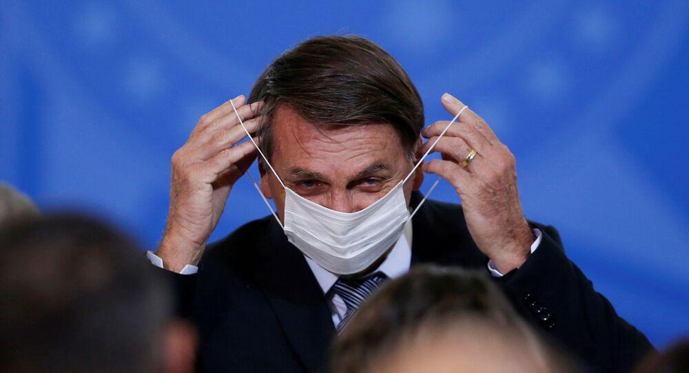 Presidente do Brasil, Jair Bolsonaro, coloca máscara durante cerimônia no Palácio do Planalto, em Brasília, 8 de abril de 2021