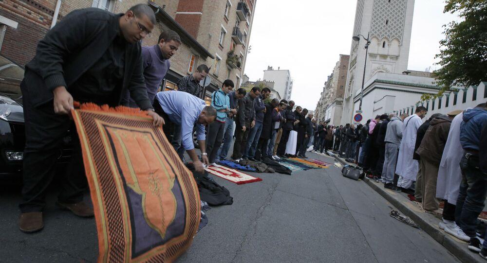 Os muçulmanos colocam seus tapetes de oração na rua em frente à mesquita em Paris, sexta-feira, 26 de outubro de 2012