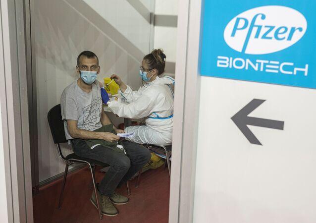 Homem recebe segunda dose da vacina da Pfizer/BioNTech contra a doença a COVID-19 em Belgrado, Sérvia, 13 de abril de 2021