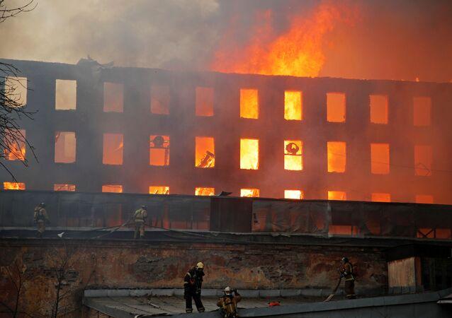Bombeiros trabalham para apagar incêndio na fábrica Nevskaya Manufaktura, no centro de São Petersburgo, na Rússia, no dia 12 de abril de 2021