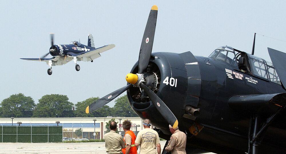 Um avião da Segunda Guerra Mundial F4U Corsair, à esquerda, faz um voo rasante próximo de um TBM Avenger