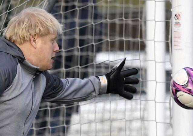 Em Cheadle Hulme, na Inglaterra, o primeiro-ministro do Reino Unido, Boris Johnson, brinca como goleiro durante campanha antes de uma partida local entre times infantis femininos, em 7 de dezembro de 2019