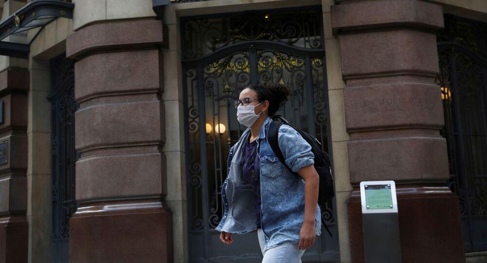 Mulher com máscara caminhando no centro de São Paulo durante a pandemia da COVID-19.