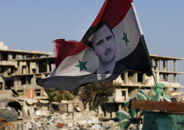 Bandeira nacional da Síria com foto de Bashar Assad, presidente do país, voando em um posto de controle do Exército sírio, na cidade de Douma, perto de Damasco, Síria, 15 de julho de 2018