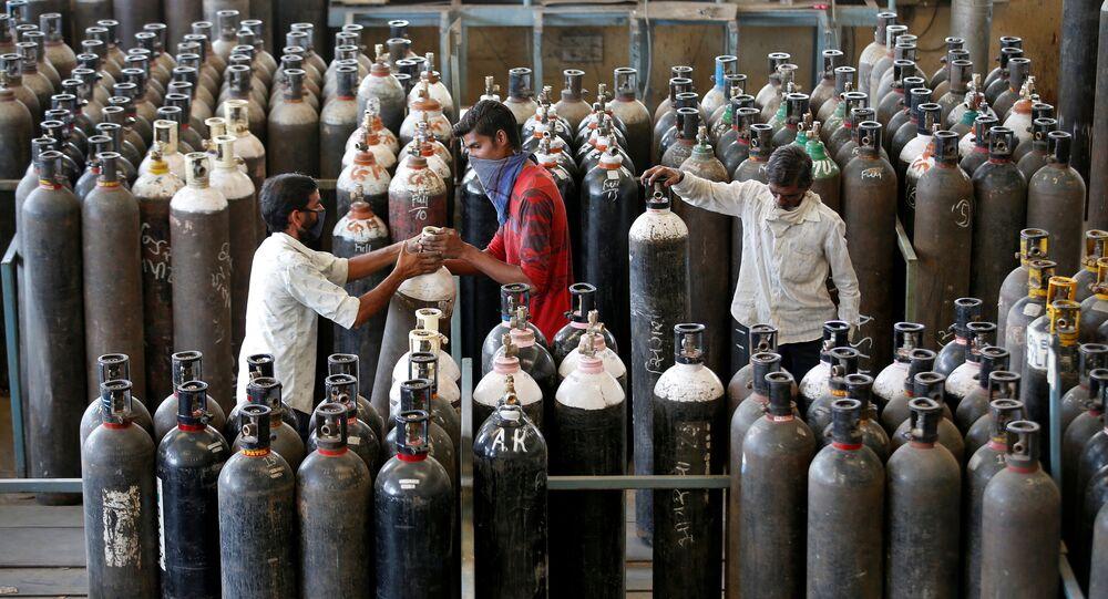 Em Ahmedabad, na Índia, pessoas carregam cilindros de oxigênio após enchê-los em uma fábrica em meio ao pico da pandemia da COVID-19 no país, em 25 de abril de 2021