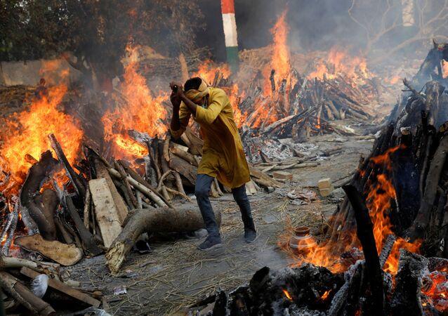 Em Nova Deli, na Índia, um homem corre em meio a piras funerárias em meio a uma cremação em massa de corpos de pacientes infectados com a COVID-19, em 26 de abril de 2021