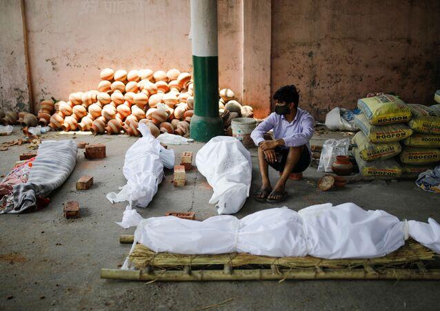 Em Nova Deli, na Índia, um homem aparece sentado próximo de corpos de pessoas infectadas com a COVID-19 enquanto aguarda a cremação dos mortos, em 26 de abril de 2021