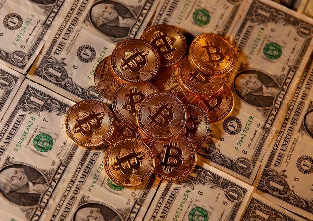 Representação da moeda virtual bitcoin e notas de dólar americano