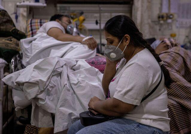 Mulher sentada ao lado de seu marido, que sofre da doença do novo coronavírus (COVID-19), dentro da sala de emergência do hospital Sagrada Família em Nova Deli, Índia, 29 de abril de 2021