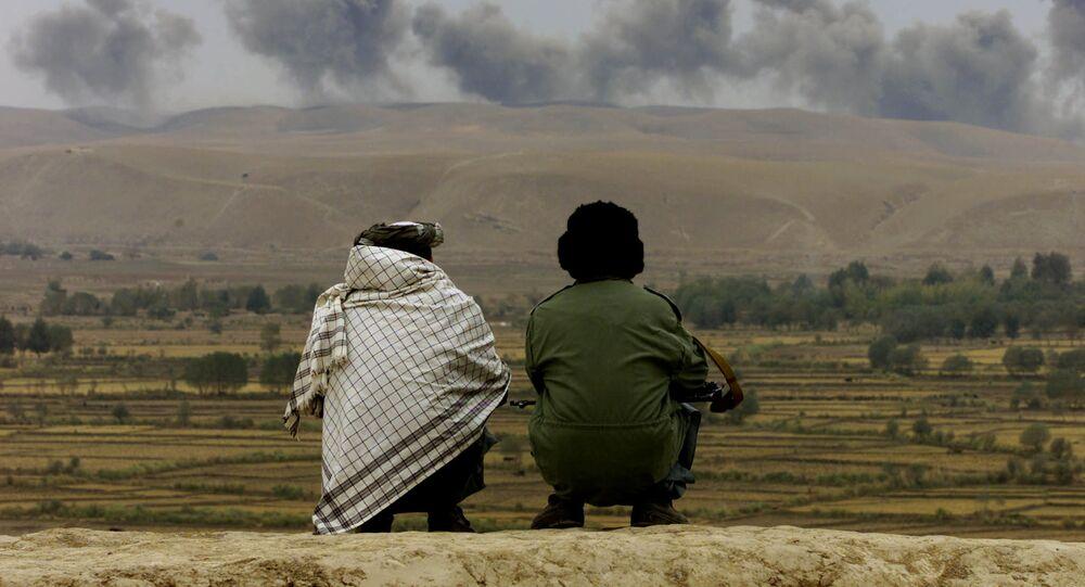 Em Ai-Khanum, nordeste do Afeganistão, dois soldados da aliança do norte assistem enquanto explosões surgem no horizonte, em 1º de novembro de 2001