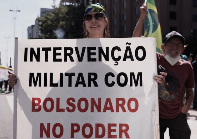 Em São Paulo, manifestante bolsonarista segura faixa pedindo intervenção militar no Brasil, em 1º de maio de 2021
