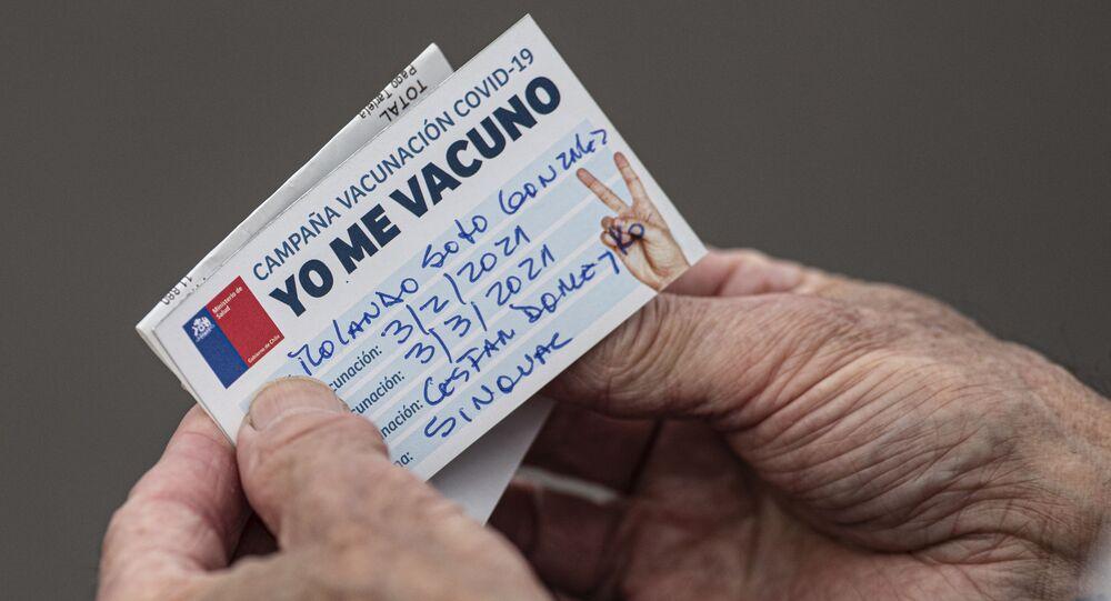 Um senhor chileno olha para seu cartão de vacinação após receber uma injeção da CoronaVac, em Santiago, no dia 3 de fevereiro de 2021