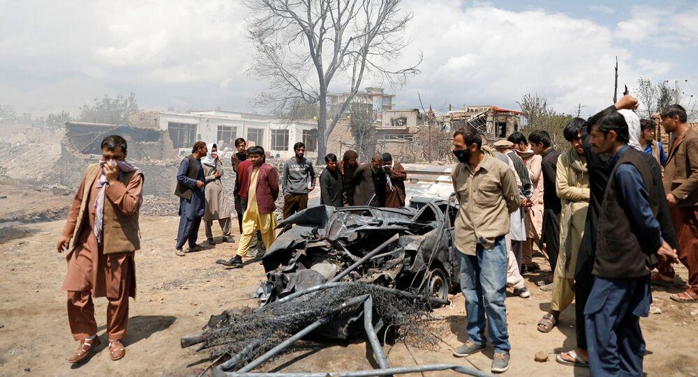 Homens inspecionam carro queimado após um incêndio noturno nos arredores de Cabul, Afeganistão, 2 de maio de 2021
