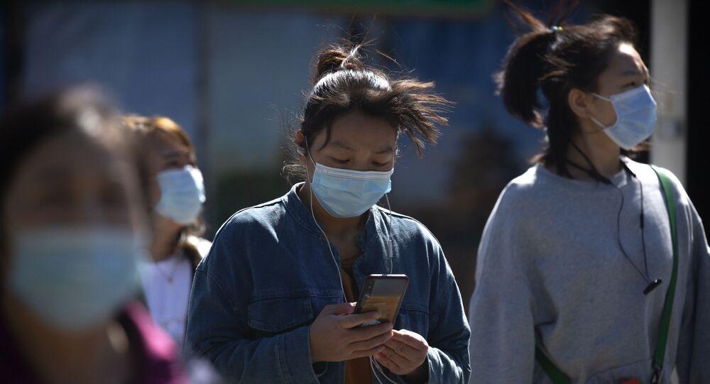 Pedestres usam máscara protetora nas ruas da capital chinesa, Pequim, 7 de março de 2021