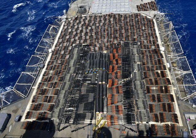 Milhares de armas ilícitas são exibidas a bordo do cruzador de mísseis guiados USS Monterey (CG 61), apreendidas de um dhow apátrida em águas internacionais do mar da Arábia