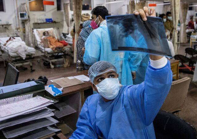 Médico responsável pelos pacientes com COVID-19 observa raio-X durante turno de 27 horas em hospital em Nova Deli, Índia, 1º de maio de 2021
