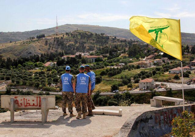 Membros da força de paz da ONU perto de uma bandeira do Hezbollah monitorando a situação na fronteira entre Líbano e Israel