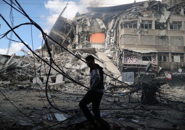 Homem caminha em frente à prédio destruído em ataque aéreo israelense contra a Faixa de Gaza