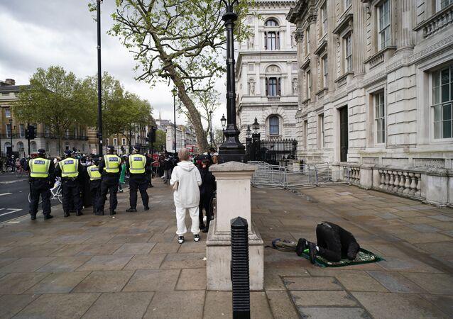 Um homem reza enquanto manifestantes se reúnem para um ato de apoio aos palestinos em Londres, na Inglaterra, neste sábado, 15 de maio de 2021