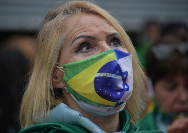 Mulher usa máscara com bandeiras do Brasil e Israel durante manifestação de apoio ao presidente Jair Bolsonaro, Brasília, 15 de março de 2021