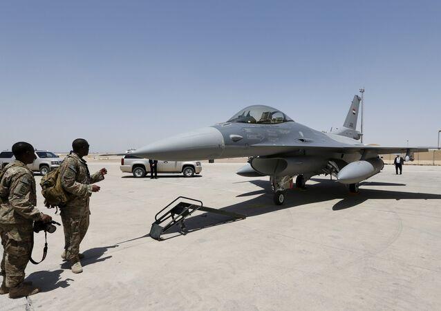 Em Balad, no Iraque, soldados observam um caça F-16 em base militar dos Estados Unidos durante uma cerimônia de entrega das aeronaves, em 20 de julho de 2015