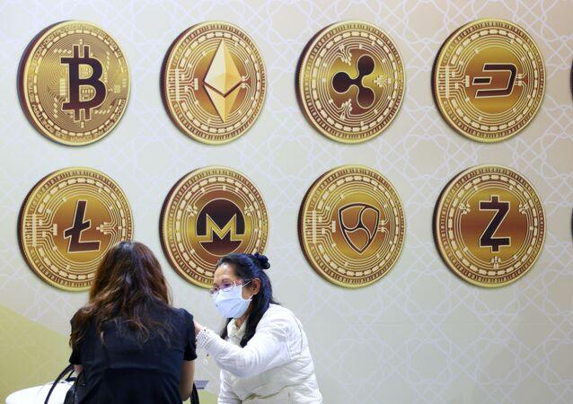 Mulheres conversam perto de uma parede com símbolos de criptomoeda em Taipé, Taiwan. Foto do arquivo
