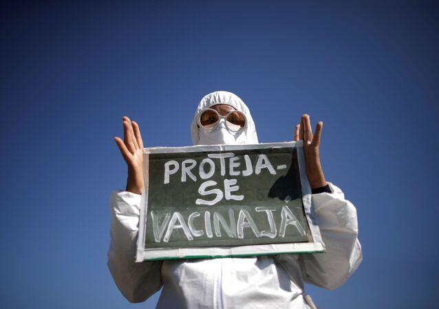 Manifestante segura cartaz com mensagem Proteja-se, vacina já durante protesto antigovernamental organizado contra o presidente brasileiro Jair Bolsonaro, Brasília, 26 de maio de 2021