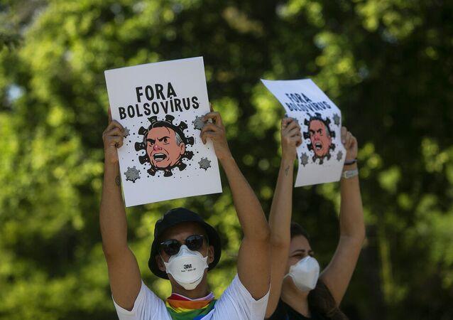 Manifestantes usando máscaras seguram cartazes retratando o presidente Jair Bolsonaro como um vírus durante protesto contra a resposta do governo federal no combate à COVID-19, no Rio de Janeiro, Brasil, sábado, 29 de maio de 2021