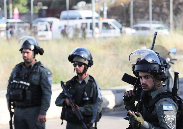 Forças de segurança israelenses seguram no local de um incidente na entrada do bairro Sheikh Jarrah, em Jerusalém Oriental, em 16 de maio de 2021