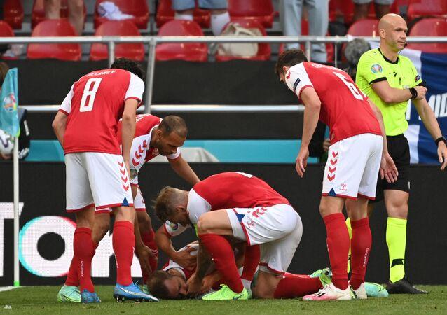 Jogadores da Dinamarca socorrem o meio-campista Christian Eriksen depois que ele desmaiou em campo antes da chegada dos médicos durante a partida de futebol do Grupo B da Eurocopa 2020 entre Dinamarca e Finlândia, no Estádio Parken, em Copenhague, em 12 de junho de 2021